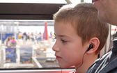 Little boy listening to the tour description on a excursion bus — Stock Photo