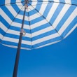 Beach background with stripy umbrella — Stock Photo #12872552