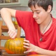 Father and son carving Halloween pumpkin on a kitchen table — Stock Photo