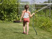 Girl is watering the garden — Stock Photo