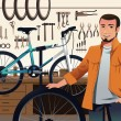 Bicycle store owner in his bike repair shop — Stock Vector