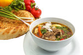 Kharcho soup with bread and vegetables — Stock Photo