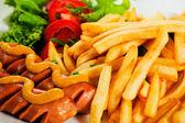 Potatoes fries and sausage — Stock Photo