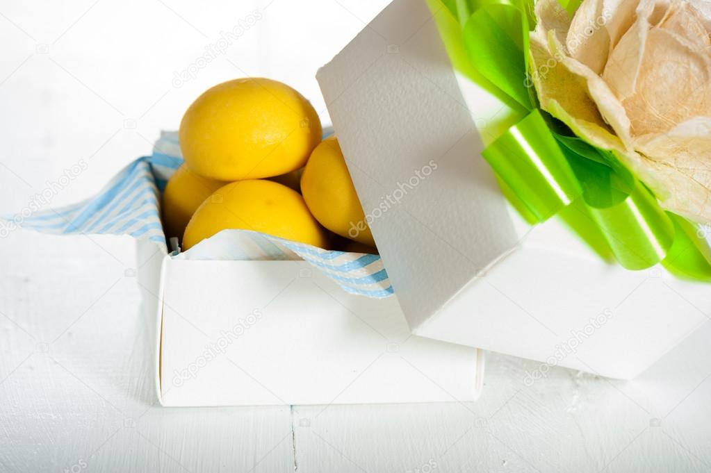 Yellow fondant cookies ball in a gift box and a rose as decoration on top,on white background — Stock Photo #13607892