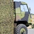 Military vehicle hung with camouflage netting — Stock Photo