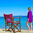 Pretty sexy caucasigirl in purple dress on beach chair on shore near sea — Stock Photo #13315378