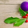 Christmas holly berry with red berries on wood with ball decoration - Stock Photo