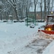 Snowplow Tractor cleaning snow in the park — Stock Photo