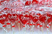 Red heart shaped lollipop on a market stand — Stock Photo