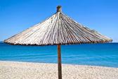 Ombrellone di paglia sulla spiaggia con cielo blu — Foto Stock