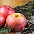 Red winter apples with cinnamon sticks — Stock Photo