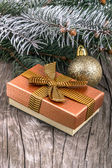 Gift box with golden ribbon and Christmas decoration over wooden table — Stockfoto