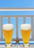 Beer glass on terrace with star fish — Stock Photo