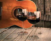 Guitar and Wine on a wooden table romantic dinner background — Stock Photo