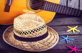 Acoustic guitar star hat and starfish on a grunge wood summer background — Стоковое фото