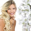 Blond woman with blooming flowers — Stock Photo