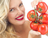 Smiling woman with tomatos — Stock Photo
