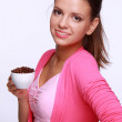 Young woman holding a cup of coffee beans - Stock Photo