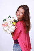 Beautiful brunette in a pink blouse with a bouquet — Stock Photo