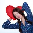 Picture of happy and smiling woman with heart-shaped pillow — Stock Photo