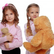 Two girls playing with bear — Stock Photo