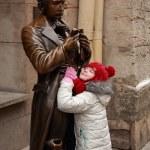 chica bonita en un gorro de punto rojo y chaqueta con el monumento de sacher-masoch — Foto de Stock