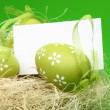 Easter color eggs in nest with card — Stock Photo