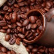 Roasted coffee beans with ceramic dark brown coffee cup — Stock Photo