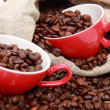 Coffee beans in ceramic red cup with heart symbol over burlap sack — Stock Photo #23831601