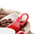 Coffee beans in red cup with heart symbol over burlap sack — Stock Photo