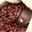 Roasted coffee beans with ceramic cup over burlap coffee bag — Stock Photo