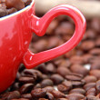 Coffee beans in ceramic red coffee cup with heart symbol — Stock Photo #23834571