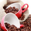 Coffee beans in red cup with heart symbol over burlap sack — Foto de Stock