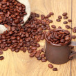Dark brown coffee beans with ceramic cup — Stock Photo
