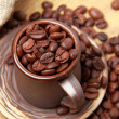 Dark brown coffee beans with ceramic cup — Stock Photo #23835723