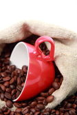 Coffee beans in coffee cup with heart symbol over burlap sack — Stock Photo