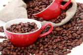 Coffee beans in red cups with heart symbol over burlap sack — Stock Photo
