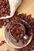 Dark brown coffee beans with ceramic coffee cup — Stock Photo