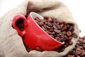 Granos de café en taza roja con el símbolo del corazón sobre arpillera — Foto de Stock