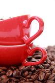 Granos de café en la taza de café rojo con el símbolo del corazón — Foto de Stock