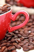 Coffee beans in ceramic red coffee cup with heart symbol — Stock Photo