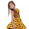 Charming emotional little girl in a yellow dress — Stock Photo