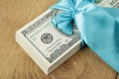 One hundred dollars gift pack isolated on wooden background — Stock Photo