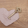 图库照片: Ancient key with ornament and paper heart on wooden background