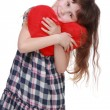 Cute little girl in checkered dress holding toy heart — Stock Photo