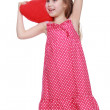 Cheerful little girl in a dress holding a toy heart — Stock Photo #24325309