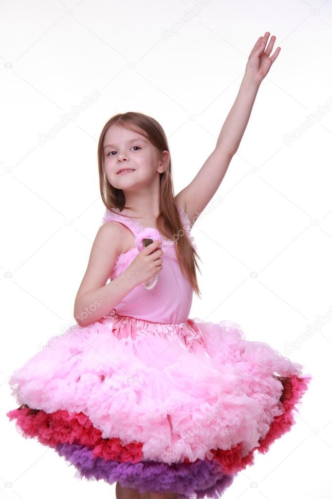 漂亮的小女孩穿着可爱粉色衣服跳舞在白色背景上孤立