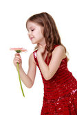 Charming little girl with light make-up and a beautiful dress holding a pink gerbera — Stock Photo