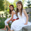 Lovely girls with basket of red apples on a bench - Foto de Stock