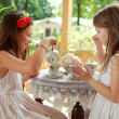 Outdoor image of beautiful little girls with tea — Stock Photo